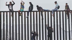 Miembros de la caravana de migrantes que cruzó México a pie hasta la frontera con Estados Unidos trepan el muro fronterizo que separa ambos países el pasado 29 de abril del 2018.