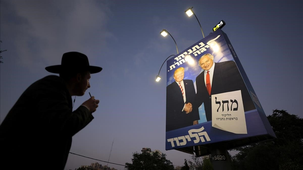 Un judío ultraortodoxo pasa en Jerusalénjunto a un cartel electoral de Netanyahu en el que aparece con el presidente de EEUU, Donad Trump.