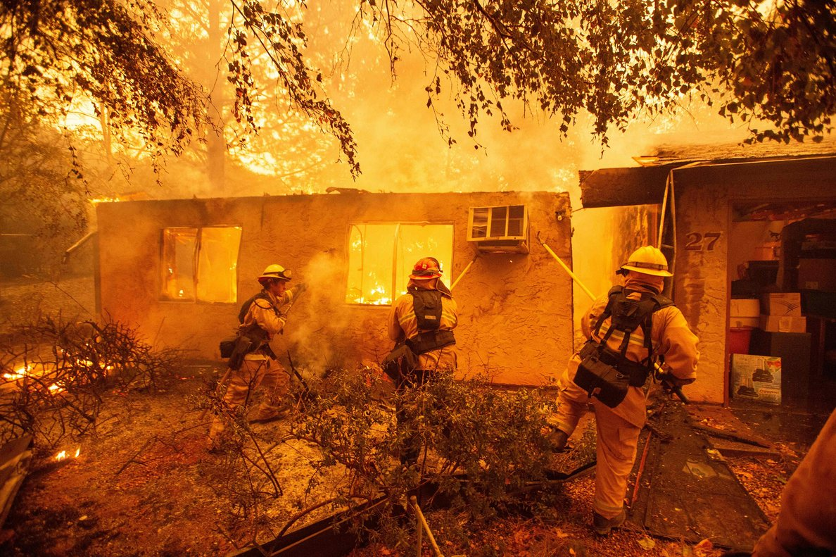 TOPSHOT - Firefighters push down a wall while battling against a burning apartment complex in Paradise, north of Sacramento, California on November 09, 2018. - A rapidly spreading, late-season wildfire in northern California has burned 20,000 acres of land and prompted authorities to issue evacuation orders for thousands of people. As many as 1000 homes, a hospital, a Safeway store and scores of other structures have burned in the area as the Camp fire tore through the region. (Photo by Josh Edelson / AFP)