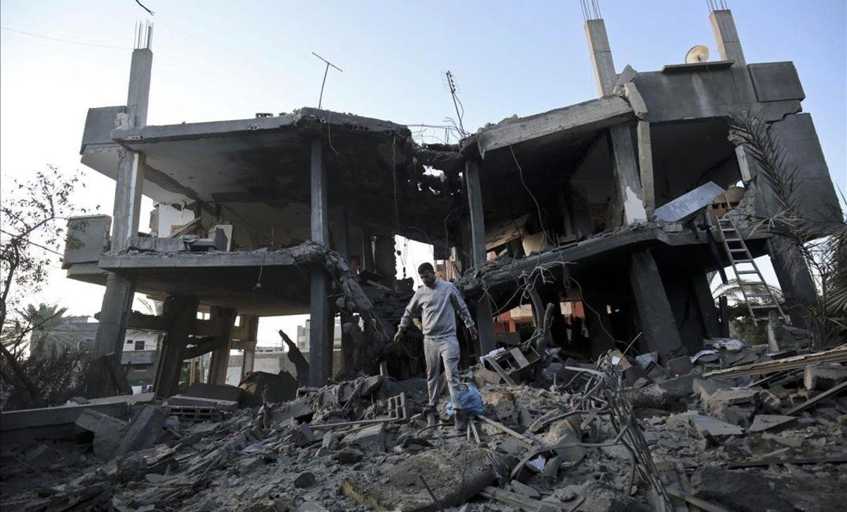 Palestinos caminan en una zona destruida por los ataques aéreos israelís en Khan Yunis, en el sur de Gaza.