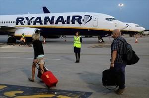 Pasajeros de Ryanair trasladando el equipaje a la aeronave.
