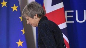 La primera ministra británica, Theresa May, pasa ante las banderas de la UE y del Reino Unido tras celebrar una rueda de prensa en Bruselas.