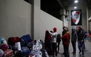 Personas en situación de calle en Buenos Aires se refugian del fríoen el estadio de River Plate.