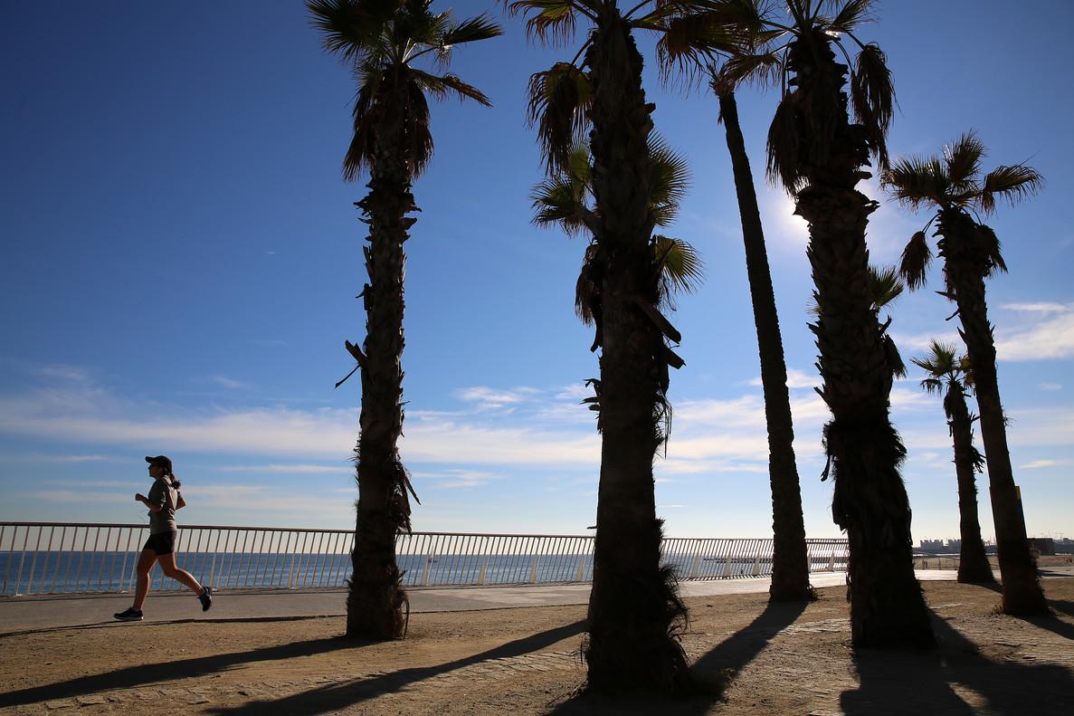 Una persona corre junto a la costa en una mañana soleada.