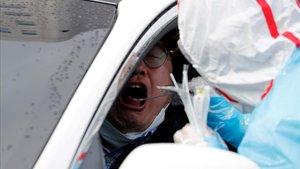 Un sanitario toma muestras a un conductor en Daegu, Corea del Sur.