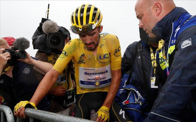 Julian Alaphilippe busca el apoyo de las vallas tras llegar muy agotado a la cima de Prat d'Albis.