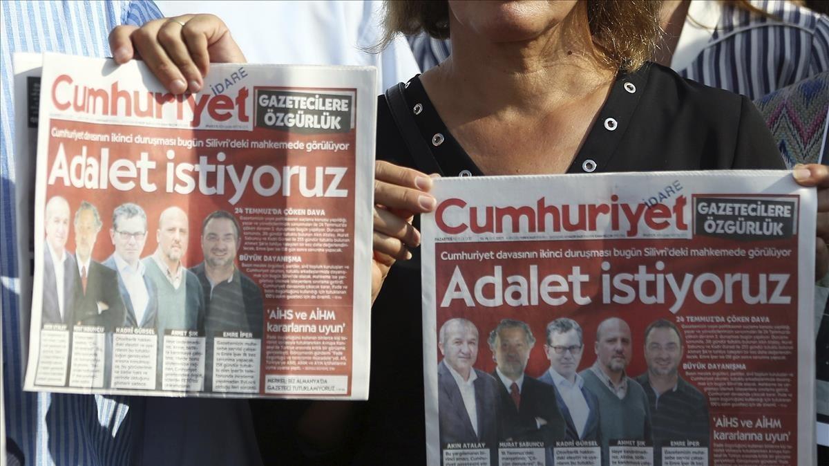 Dos personas muestran las portadas del periódico Cumhuriyet frente a la prision de Silivri dondese celebra el juicio contra los periodistas.