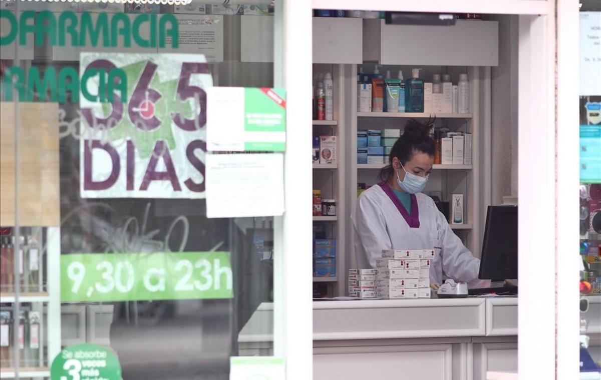 Una empleada de una farmacia de Madrid trabaja con mascarilla.