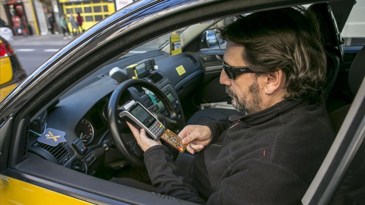 Un taxista cobra a un cliente en Barcelona.