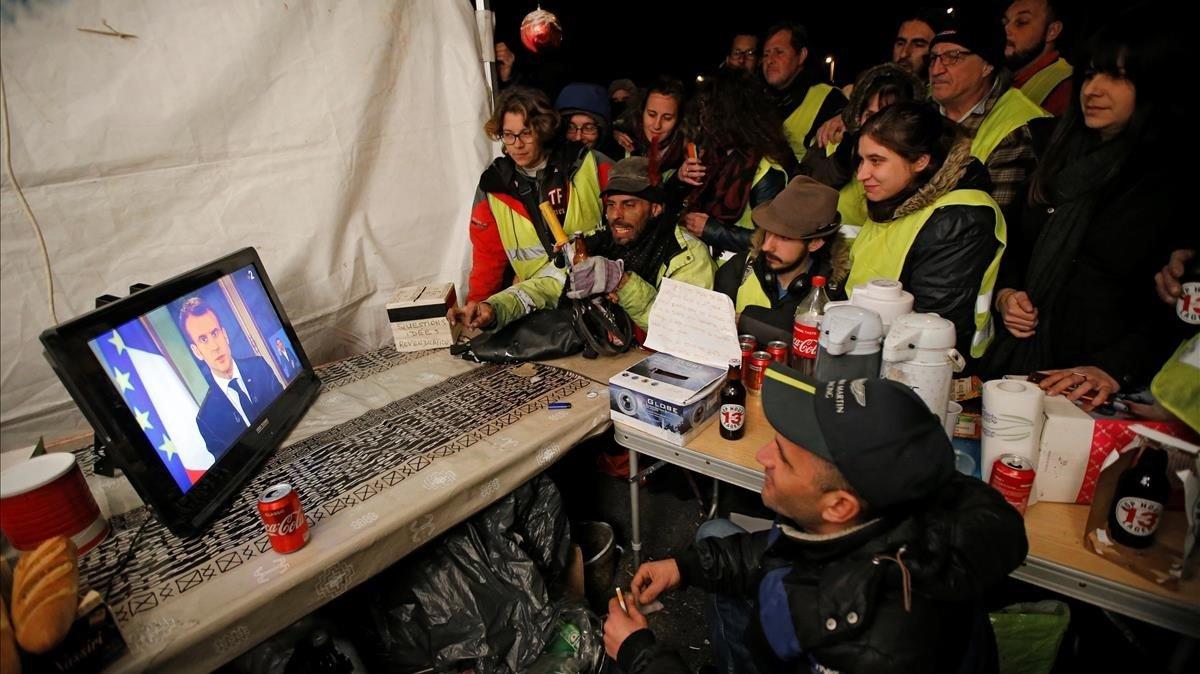 Unos 'chalecos amarillos' siguen el discurso de Macron por televisión, en La Ciotat, cerca de Marsella.