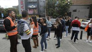 Varias personas esperan frente a los edificios tras registrarse dos terremotos demagnitudes de 6,2 y 5,7, este martes.