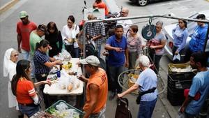 Venezolanos hacen cola para pagar la fruta y las verduras en un mercado callejero, en Caracas, el 13 de noviembre.