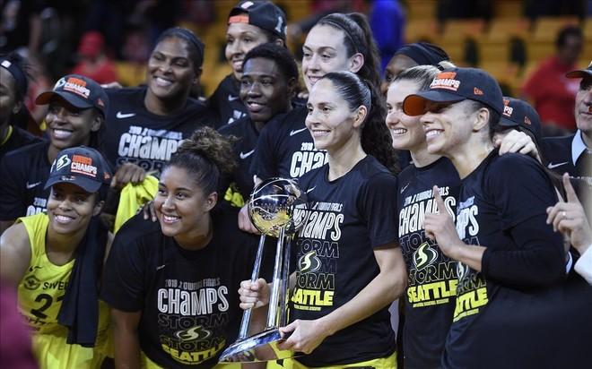 La veterana base Sue Bird sostiene el trofeo de campeonas rodeada de sus compañeras de Seattle