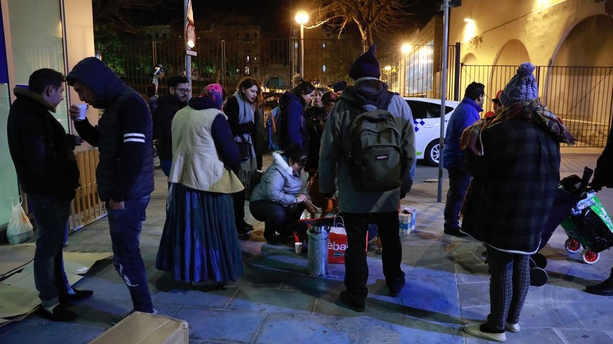 Voluntarios de una iglesia evangélica reparten cena a los sintecho de la plaza de Sant Pau.