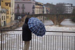 Un hombre intentando que no se le doble el paraguas por la fuerza del viento.
