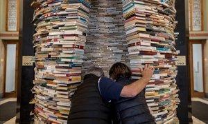 Dos personas observan la escultura titulada Idioma del artista eslovaco Matej Kren, una columna hecha de 8.000 libros, expuesta en la entrada de la Biblioteca Central de Praga (República Checa) durante la celebración del Día del Libro.