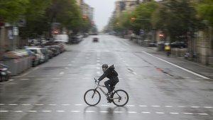 Un bici cruza la calle Aragó, sin coches, a finales del pasado mes de marzo.