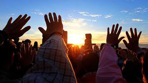 Un grupo de personas eleva sus manos en gesto de meditación durante el amanecer del solsticio de verano en las ruinas de Stonehenge (Inglaterra).