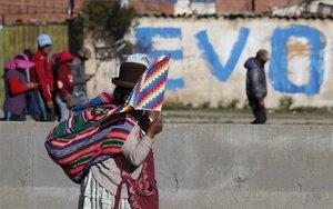 Una mujer protesta en las calles de Bolivia con la bandera indígena.