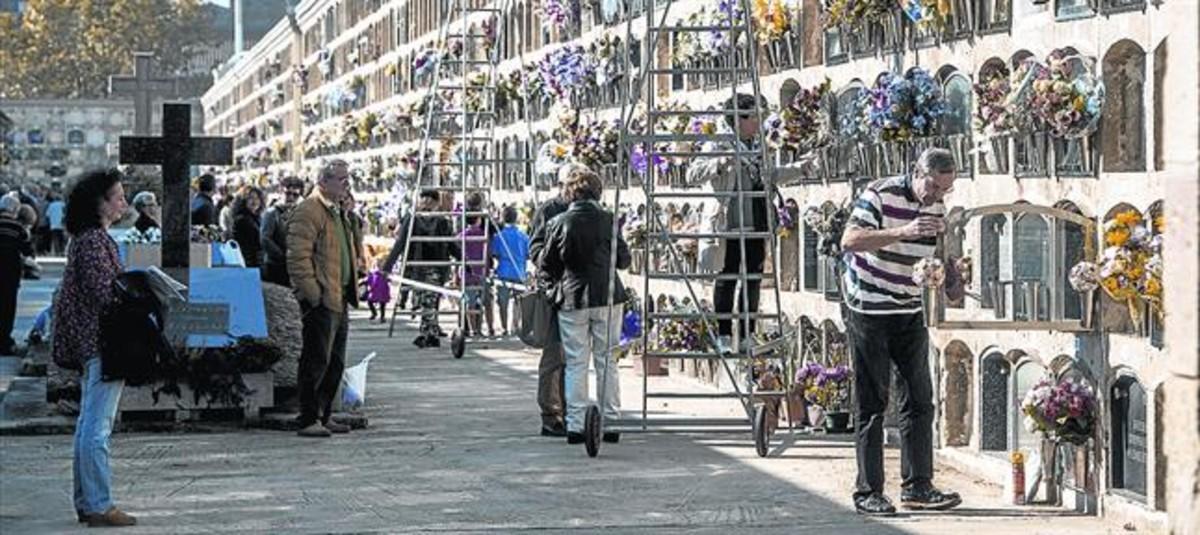 Ritual Familiares de fallecidos limpian y colocan flores en los nichos del cementerio del Poblenou, el día de Todos los Santos del 2016.