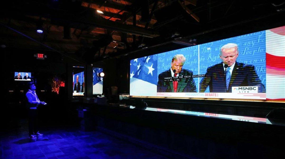 Un hombre sigue el debate en televisión en un bar de West Hollywood, California.