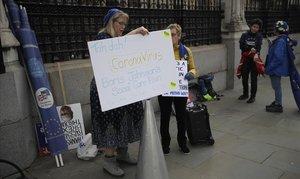 Detractoras del 'brexit' exhiben ante el Parlamento británico pancartas relacionándolo con la estrategia de Boris Johnson para combatir el coronavirus.