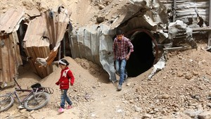 Dos niños salen de un pasadizo subterráneo en la bombardeada Duma, en la región siria de Guta Oriental, el 17 de abril.