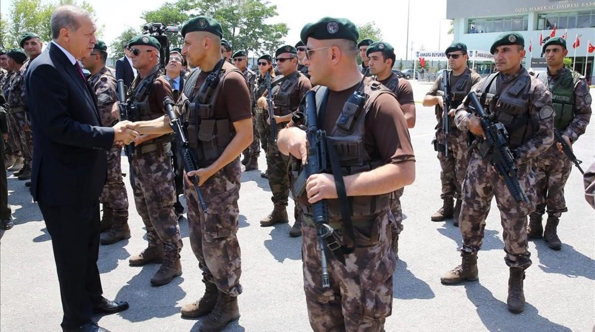 Erdogan (izquierda) saluda a un agente durante su visita al cuartel general del departamento policial de operaciones especiales, en Ankara, el 29 de julio.