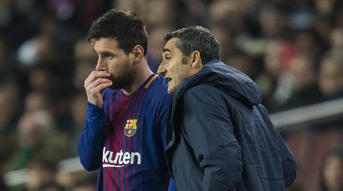 Ernesto Valverde y Leo Messi conversan en un descanso deun partido.