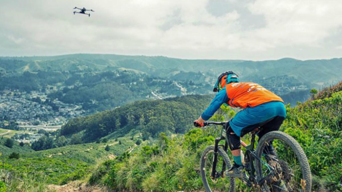 Un ciclista de montaña seguido de cerca por su dron autónomo Airdog.