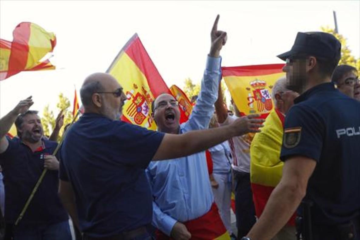 Un grupo de personas increpan a los asistentes a la asamblea convocada por Unidos Podemos.