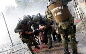Un herido es trasladado por las fuerzas de seguridad durante las protestas en Santiago.