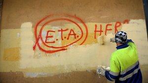 Un operario borra una pintada en la que aún se puede leer ETA, en una imagen de asrhivo