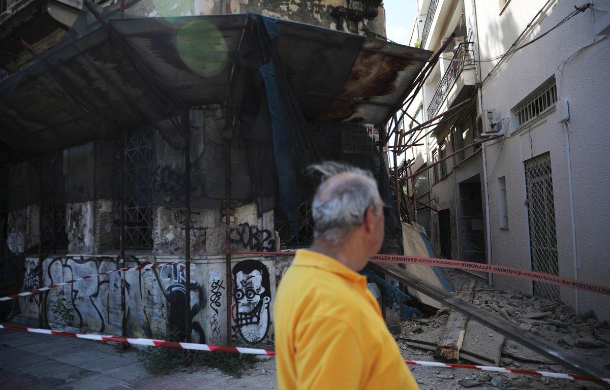 Un hombre camina por delante de los daños provocados por el terremoto deAtenas en un edificio.