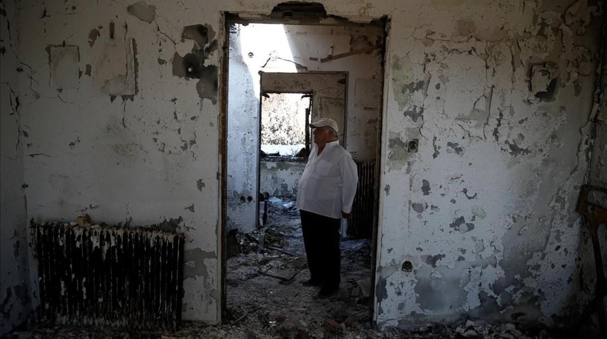 Un hombre en su casa quemada de Mati.