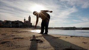 Un hombre hace ejercicio en la playa de Sitges.
