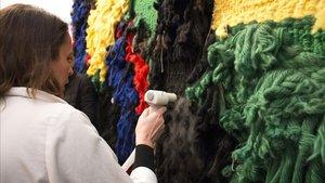La jefa del equipo de restauración, Elisabet Serrat, pasa el humidificador por el dorso del tapiz.