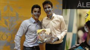 Marc y Àlex Márquez sostienen en sus manos el libro que relata el título mundial del pequeño en Moto3 del pasado año.