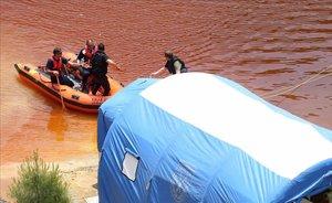 Miembros de los servicios de rescate navegan por el Lago Rojo mientras buscan nuevas pistas de los crímenes.