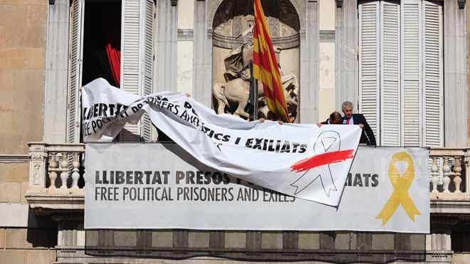 Momento en el que se cambia la pancarta con el lazo amarillo por otra con un lazo blanco en la Generalitat.