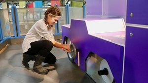 Una niña juega a reparar un coche en el museo Explora de Roma.
