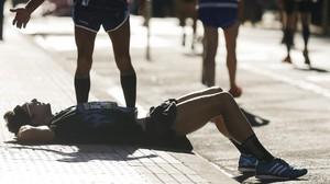 Un participante descansa en la acera tras acabar la Behobia-San Sebastián este domingo.