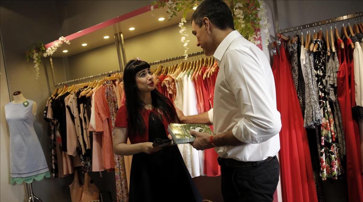 Pedro Sánchez entrega propaganda electoral en una tienda del centro de Madrid, este martes.