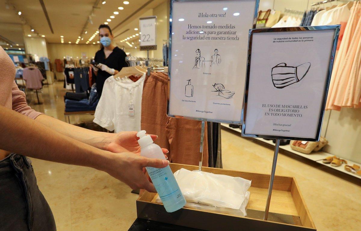 Una mujer usa el gel hidroalcohólico antes de entrar en una tienda de ropa.
