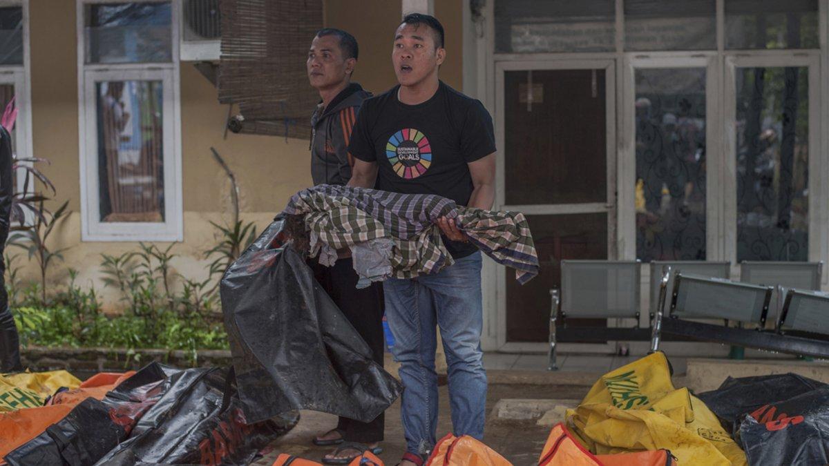 Un voluntario lleva en brazos el cadáver de un niño en Carita (Indonesia).