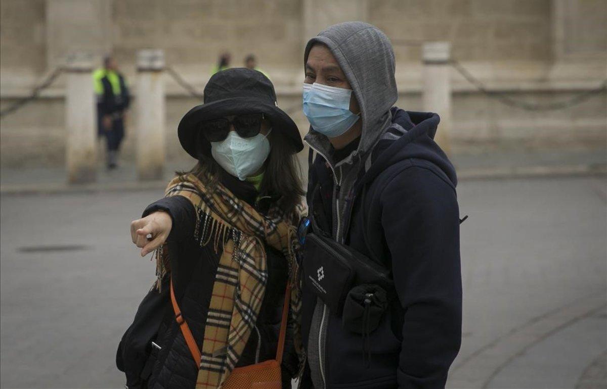 Turistas con mascarillas para protegerse del coronavirus pasean por Sevilla.