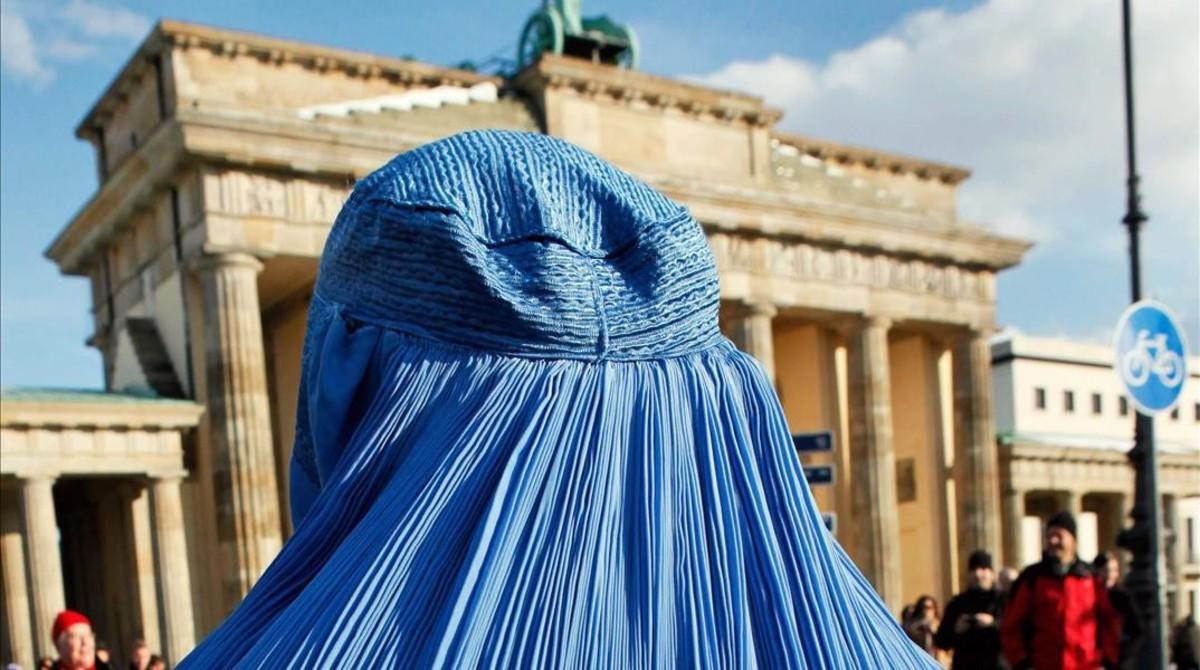 Una mujer, con burka, frente a la puerta de Brandeburgo, en Berlín.