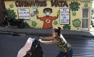 Una mujer empuja un carro de bebé ante un cartel que pide precaución frente al coronavirus en el Complexo do Alemão, una barriada de favelasen Rio de Janeiro.