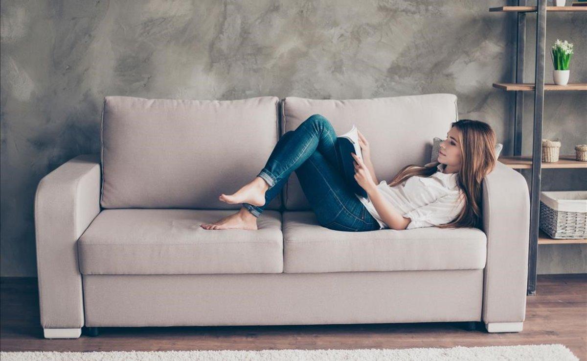 Una mujer tranquila en su casa leyendo.