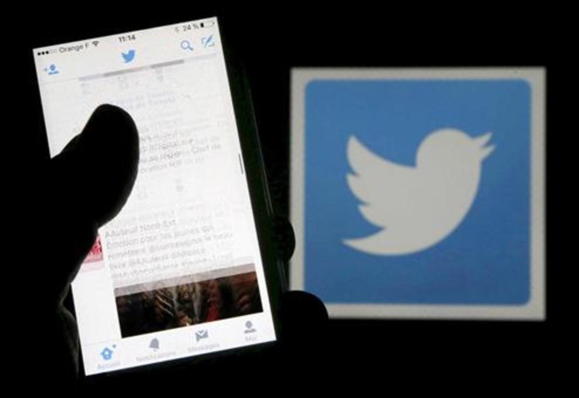 Un usuario de Twitter lee mensajes de esta red social en el móvil frente al logo del pájaro, símbolo de la misma.